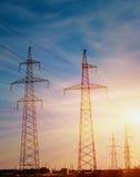 Elektriciteitspylonen tegen de zonsondergang worden gesilhouetteerd die stock afbeelding