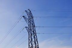 Elektriciteitspyloon met machtskabels tegen blauwe hemelachtergrond stock foto