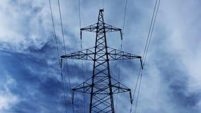 Elektriciteitspyloon met stormachtige hemel op de achtergrond Elektropyloon met timelapsewolken stock videobeelden