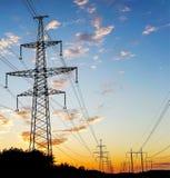 Elektriciteitspyloon - standaard lucht de transmissietoren van de machtslijn bij zonsondergang Stock Foto's
