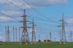 Elektriciteitspyloon tegen blauwe backgrou die van de hemelzonneschijn wordt gesilhouetteerd stock fotografie