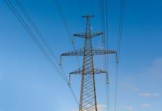 Elektriciteitspyloon tegen blauwe hemelachtergrond die wordt gesilhouetteerd De toren van de hoogspanning stock fotografie