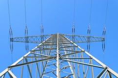 Elektriciteitspyloon tegen duidelijke blauwe de winterhemel Stock Afbeeldingen