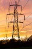 Elektriciteitspyloon tegen een mooie zonsondergang wordt gesilhouetteerd die Royalty-vrije Stock Afbeelding