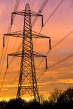 Elektriciteitspyloon tegen een zonsondergang wordt gesilhouetteerd die Stock Afbeelding