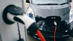 Elektricitet laddar upp en svart bil arkivfilmer