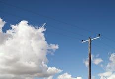 Elektricitet Pole på den blåa skyen och fluffiga oklarheter Arkivbild
