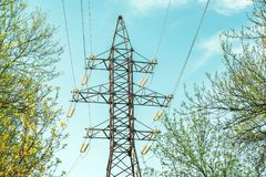 Elektricitetsöverföringskraftledning i de ljusa strålarna av solen på bakgrund för blå himmel Hög-spänning elektriskt torn bland  Royaltyfri Bild