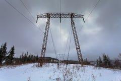 Elektricitetsöverföringskraftledningar på hög spänning för vinterbakgrund står högt Pylon för metallelektricitetsöverföring Arkivfoto
