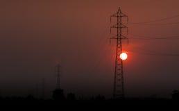 Elektricitetsöverföringspylon i fältet på solnedgång Royaltyfri Foto