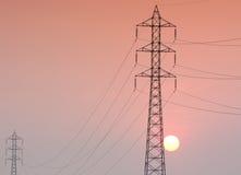 Elektricitetsöverföringspylon i fältet på solnedgång Fotografering för Bildbyråer