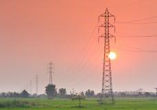 Elektricitetsöverföringspylon i fältet på solnedgång Arkivbild