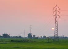 Elektricitetsöverföringspylon i fältet på solnedgång Royaltyfri Bild