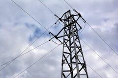 Elektricitetsöverföringspylon mot molnig himmel Arkivbild