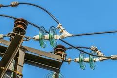 Elektricitetsgirlander av isolatorer med elektriska trådar på en bästa stålmast arkivbild