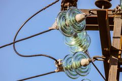 Elektricitetsgirlandnärbild av isolatorer med elektriska trådar royaltyfri foto