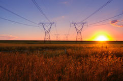 Elektricitetskraftledningar med solen på skymning Royaltyfri Bild