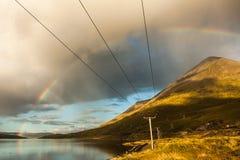 Elektricitetskraftledningar och regnbåge Arkivbild