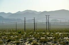 Elektricitetspoler, buskar, berg, huvudväg, Nevada Arkivbilder