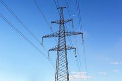 Elektricitetspylon silhouetted mot bakgrund för blå himmel Högt spänningstorn arkivbild