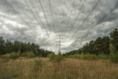 Elektricitetspyloner i fält med molnig himmel Arkivbild