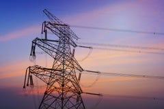 Elektricitetspyloner, kraftledningar och träd silhouetted mot en molnig himmel Arkivfoto