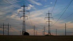 Elektricitetspyloner och aftonhimlen arkivfilmer