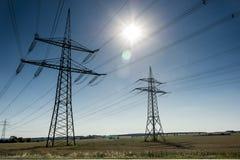 Elektricitetspyloner och fält Arkivbild