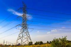 Elektricitetspyloner och linjer på ett fält Arkivfoton