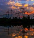 Elektricitetspyloner och linjer på skymning på solnedgången Royaltyfri Foto