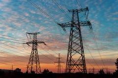 Elektricitetspyloner och linjer på skymning på solnedgången Arkivbild