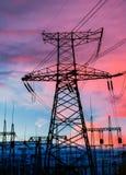 Elektricitetspyloner och linjer på skymning på solnedgången Fotografering för Bildbyråer