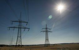 Elektricitetspyloner och sol Royaltyfri Bild