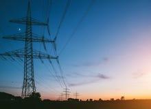 Elektricitetspyloner på solnedgången som transporterar ren energi royaltyfri bild