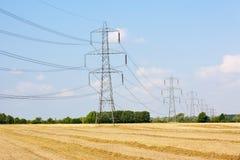 Elektricitetspylons i bygd Arkivfoto