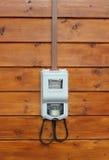 Elektricitetstillförselmeter på främre sikt för trävägg Arkivfoto