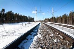Elektrifierad järnväg linje bland vintrig skog på den soliga dagen, närbildsikt på railtracken royaltyfri foto