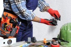 Elektriker bei der Arbeit in der Sicherheit auf einem elektrischen Wohnsystem stockfotografie
