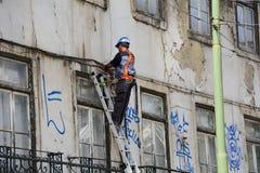 Elektriker, der alte Kabel auf Leiter repariert Lizenzfreie Stockfotos