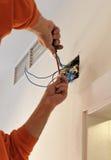 Elektriker, der die Verdrahtung während der Erneuerung des Hauses anschließt Stockbild