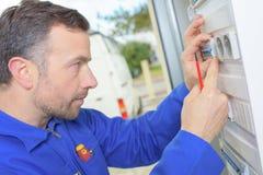 Elektriker, der ein fusebox kontrolliert stockbilder