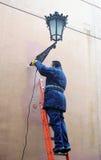 Elektriker, der eine dekorative Straßenbeleuchtung repariert Stockbilder