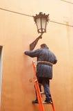 Elektriker, der eine dekorative Straßenbeleuchtung repariert Lizenzfreies Stockfoto