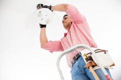 Elektriker, der eine Lampe installiert Stockfoto