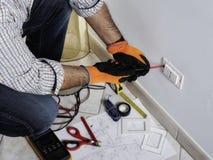 Elektriker, der in einem elektrischen Wohnsystem arbeitet lizenzfreies stockbild