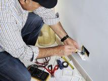 Elektriker, der in einem elektrischen Wohnsystem arbeitet lizenzfreie stockbilder