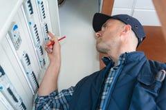 Elektriker, der fusebox betrachtet lizenzfreie stockfotografie