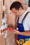Elektriker, der innerhalb des Neubaus überprüft Drähte arbeitet Lizenzfreie Stockfotografie