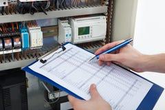 Elektriker, der Klemmbrett bei der Untersuchung von fusebox hält stockfotografie