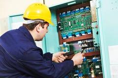 Elektriker, der Strom an der Stromleitung Kasten überprüft Lizenzfreie Stockfotografie